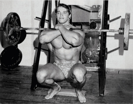 Arnold with Front Squat with Weights and a Board Under His Heels for Challenging His Balance