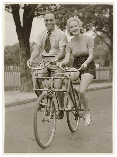 """""""Man and woman on a Malvern Star abreast tandem bicycle"""" - c. 1930s by Sam Hood."""