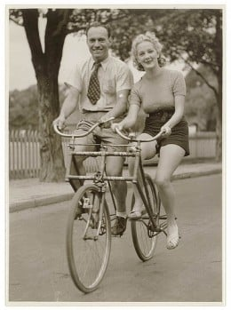 """Man and woman on a Malvern Star abreast tandem bicycle"" - c. 1930s by Sam Hood."