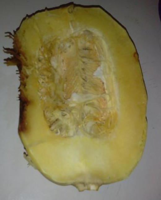 Step 2. Cut in half and remove insides. This is what it looks like cut in half. Remove inside pulp and seeds the way you would a cantaloupe or melon. FYI: The brown discoloration is where it rest on the baking pan while cooking.