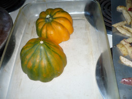 Acorn squash cut in half and put face down on the glass oven dish.