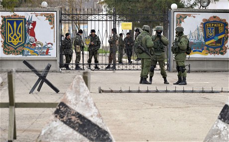 Ukrainian military personnel trapped in their own base as unmarked opposition forces stand guard.