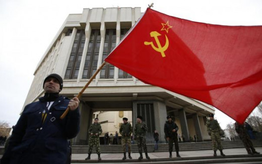 A man waves a Soviet Union flag outside the Crimean Parliament building in Simferopol.