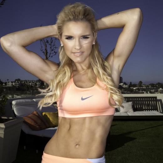 Rebecca-Louise Smith with her arms behind her head in a fitness outfit with the Nike logo showcasing strong ab muscles