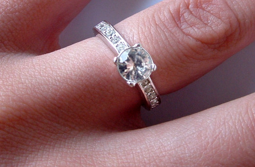 A diamond engagement ring (round brilliant cut) refracting and reflecting light.