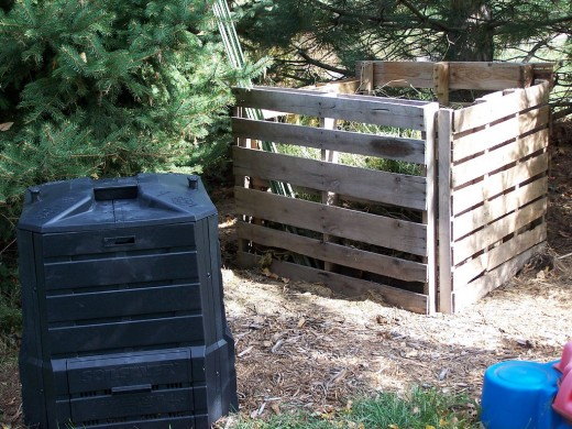 Two home / garden composting bins: a closed PVC style, and an open wooden composter.