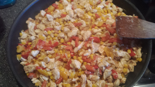 The seasoned chicken with the peppers and the sweetcorn