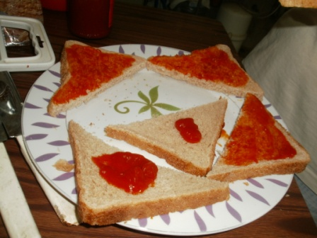 Adding pizza sauce to the sliced bread