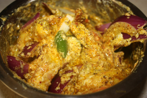 In a deep end bowl mix together marinated prawns, yogurt, mustard paste, coconut flakes, slit green chili peppers, onion slices, turmeric, salt and mustard oil and a little sugar.