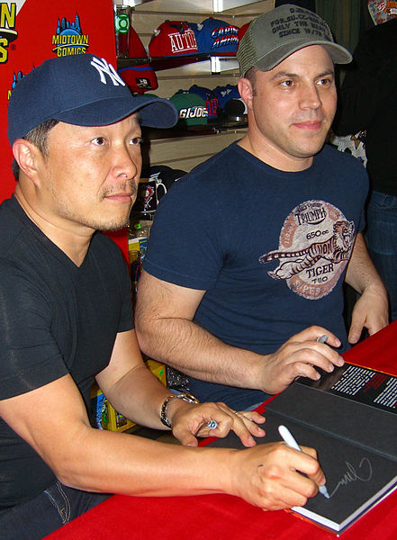 Comic book creators Jim Lee (left) and Geoff Johns (right) at a May 11, 2012 signing at Midtown Comics Downtown in Lower Manhattan for Justice League Vol. 1: Origin,