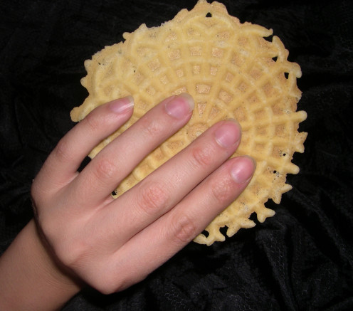 This is a picture of a Anise pizzelle that is in the person hand ready to enjoy. They really look like they will enjoy this Anise pizzelle.
