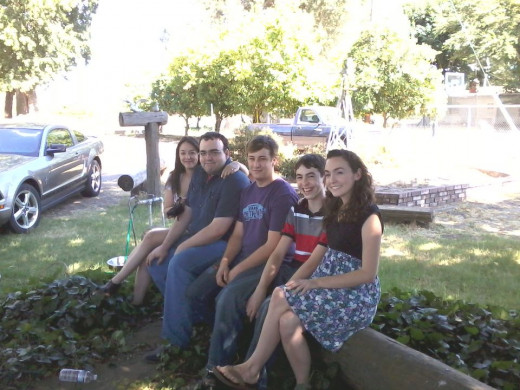 The cousins sitting on a log at the grandparents' house