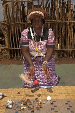 A Sangoma woman throwing divination tools for a reading.