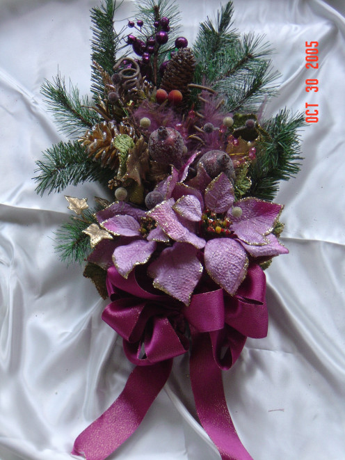 Evergreen Handmade Swag. made out of real pine and artifical poinsettias and ribbon. This homemade swag would look great on a door or any place that you want to hang a Christmas decoration in your home.