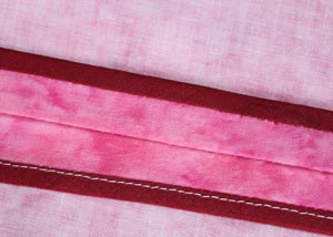 Showing how the seam will appear on the inside, note one side is hand stitched (top binding) whilst the other is machine stitched (bottom binding).