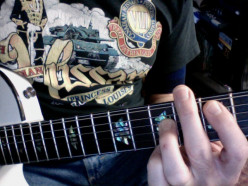 Using the edge of the second finger to mute the sixth string for Root 5 Power Chords