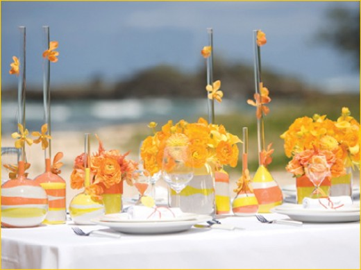 Decorate lunch/dinner tables with yellow and orange paper flowers, glass candle holder and centerpiece.