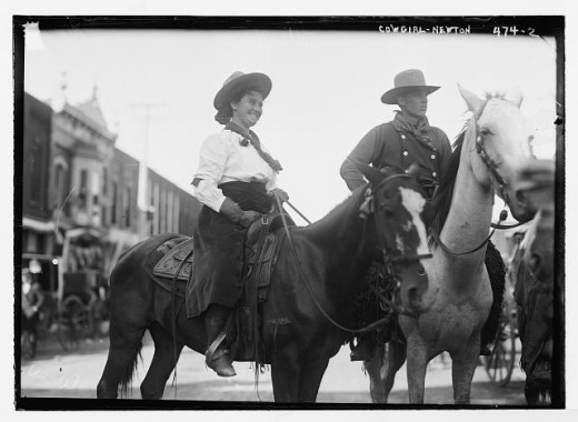 Cowgirl and cowboy on horseback, Newton, Kansas, 1908.