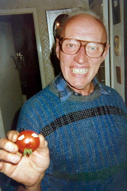 Dad in the 1990s with one of the tomatoes he had grown. I recall he was having a giggle with me, because it was a funny shape and he had stuck on eyes so it looked like a face with a little nose!