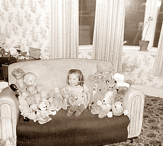Me as a little girl with my dolls and toys in the lounge of our house.