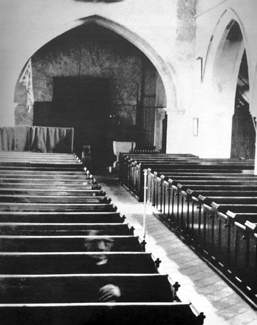 Ghostly Vicar - This photo was taken at the Eastry church near Sandwich, county of Kent in 1956. The photographer insisted that when he took the photo, the only persons in the church were his wife and the cleaning lady.