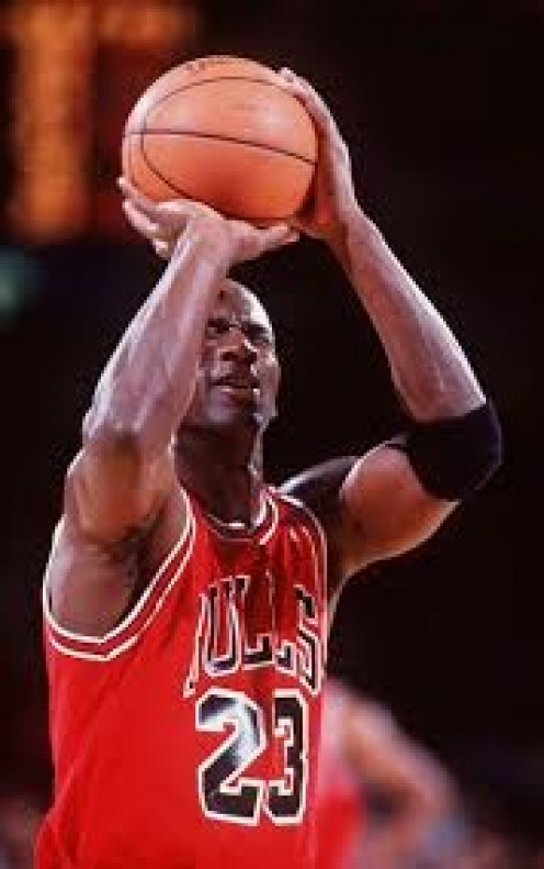 Michael Jordan is seen here shooting and making a free throw shot during a game with his eyes closed.