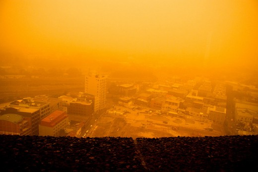 Red dust and smog seen from a rooftop.