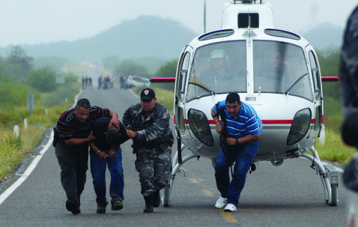 Federal Police escort drug cartel suspect from helicopter.