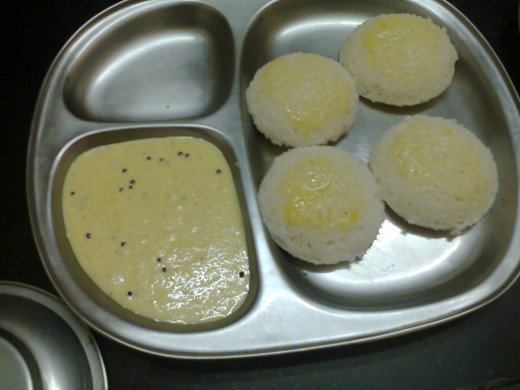 Idli (topped with cow ghee) served with Chutney in the tiffin plate