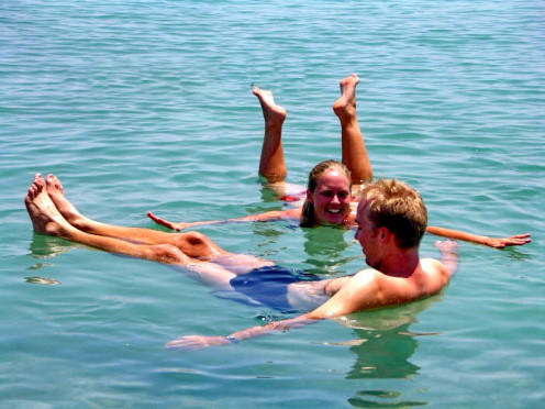 Couple floating in Dead Sea - buoyancy caused by high salinity of water