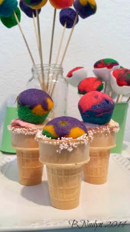Mini rainbow cupcakes can be enjoyed in so many ways, like topping them on ice cream cones.