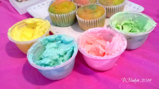 Separate Icing into small bowls and drop separate colors of the food coloring into each bowl.  Start with one drop at a time to achieve the color you want.