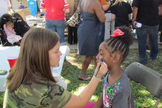 A volunteer lends her face-painting artistry to a tiny patron.