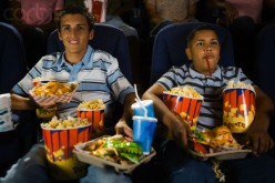 Blockng the walkway with your huge amount of food to eat during the movie.