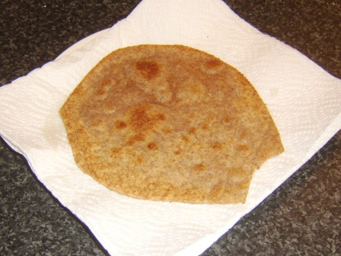 Hot paratha is briefly drained on kitchen paper