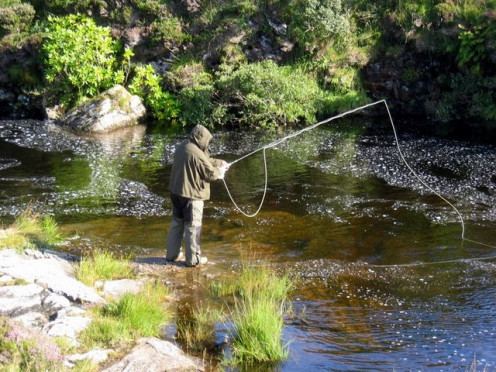 Fly fisherman covering up and braving the midges in Scotland.