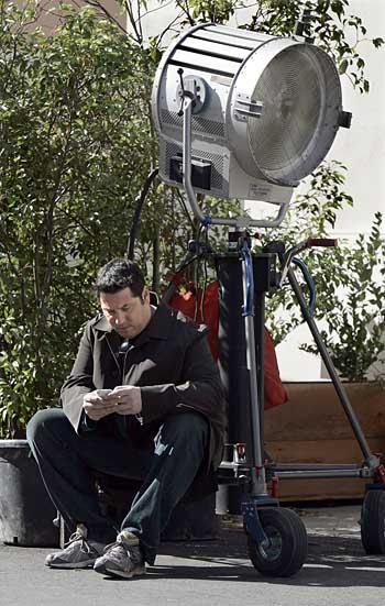"""Greg Grunberg, an actor on """"Heroes,"""" taps out a Twitter message, or tweet, on his iPhone during a break in filming. (c) Ken Hively / Los Angeles Times"""