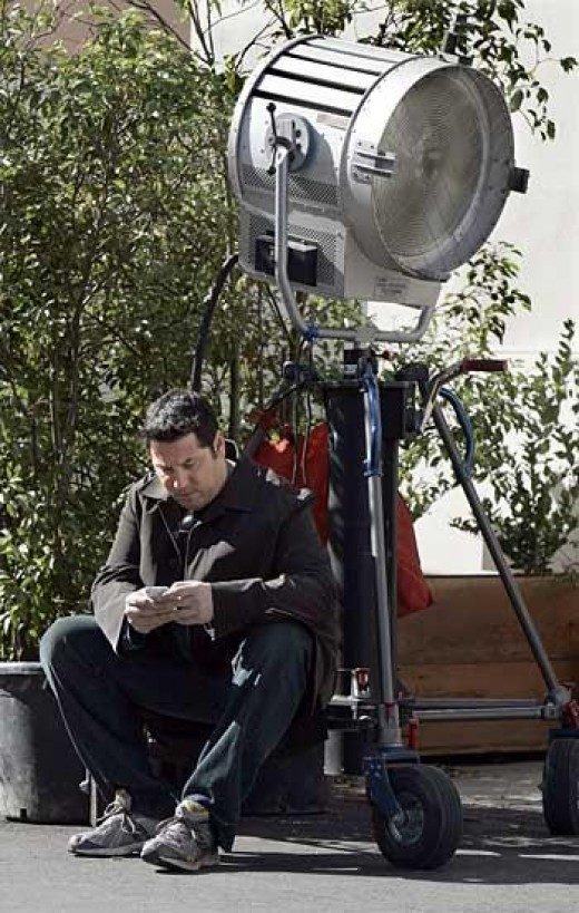 "Greg Grunberg, an actor on ""Heroes,"" taps out a Twitter message, or tweet, on his iPhone during a break in filming. (c) Ken Hively / Los Angeles Times"