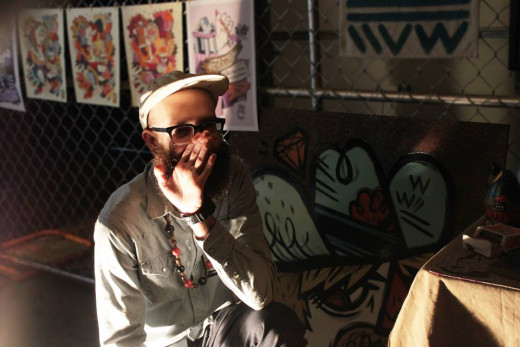 Artist Taylor McClure looks like he's telling some secrets to his work.