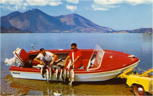 These guys, circa 1956, have had a successful fishing outing by the number of fish in the photo. Notice their hairstyles, (the men. Not the fish) and that vintage boat, typically-powered by a 3 HP Evinrude. What a great time to live in America.