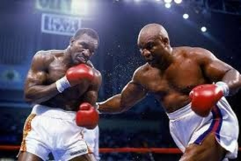"""Evander """"The Real Deal"""" Holyfield and """"Big"""" George Foreman fought a classic seventh round during their heavyweight title bout."""