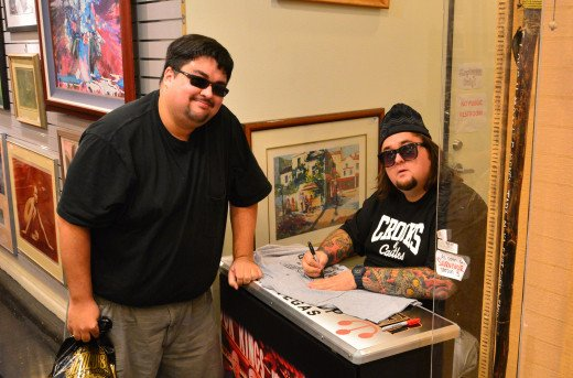 Chumlee from Pawn Stars, on the right, signing autographs like the super-star he is.