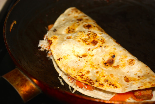 With the help of a pair of tongs or spatula fold the tortilla into two halves. Give a slight press on the top. The melted cheese will help the two halves of the tortilla to stick together. Then flip it around.