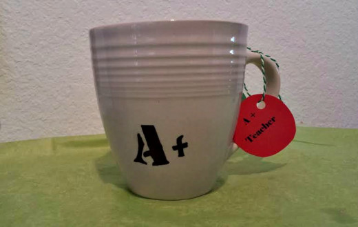 "Use a permanent marker like a Sharpie to write a message on the mug.  I used a stencil for this, as well.  I attached a red apple tag that I drew and cut myself and wrote, ""A + Teacher"" or you can write, ""Thanks a latte for teaching me."""