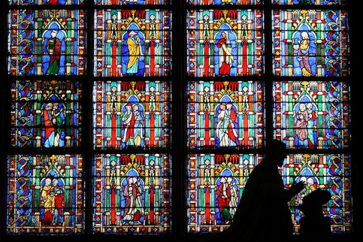 Praying priest statue in front of a stained-glass window at the Notre Dam du Paris cathedral.