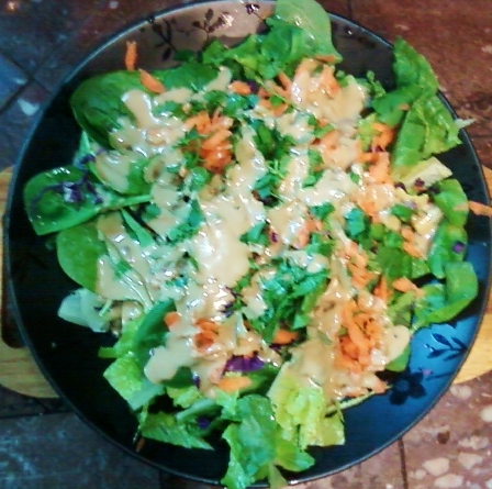 A salad topped with sesame dressing.