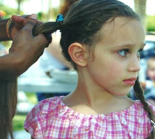 Little girl getting her hair braided.