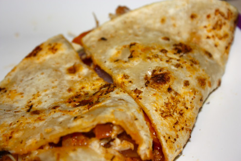 Deliver it on a serving plate. Your masala sausage quesadilla is ready. Cut it into thin wedges. Serve it with chopped onions and chili on top.