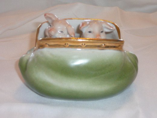 "Pigs in a purse. This is a quite common and plain version of the pigs in a purse. There are many versions of these purses including some with bears. It has a lovely gilt around the opening. 4"" x 3"". Paid $38. Common."
