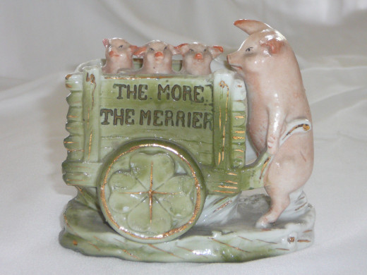 "The More the Merrier. Three pigs in a wheelbarrow being pushed by their mommy. Notice the shamrock in the wheel. 4"" x 3 1/2"". $77. Rare."